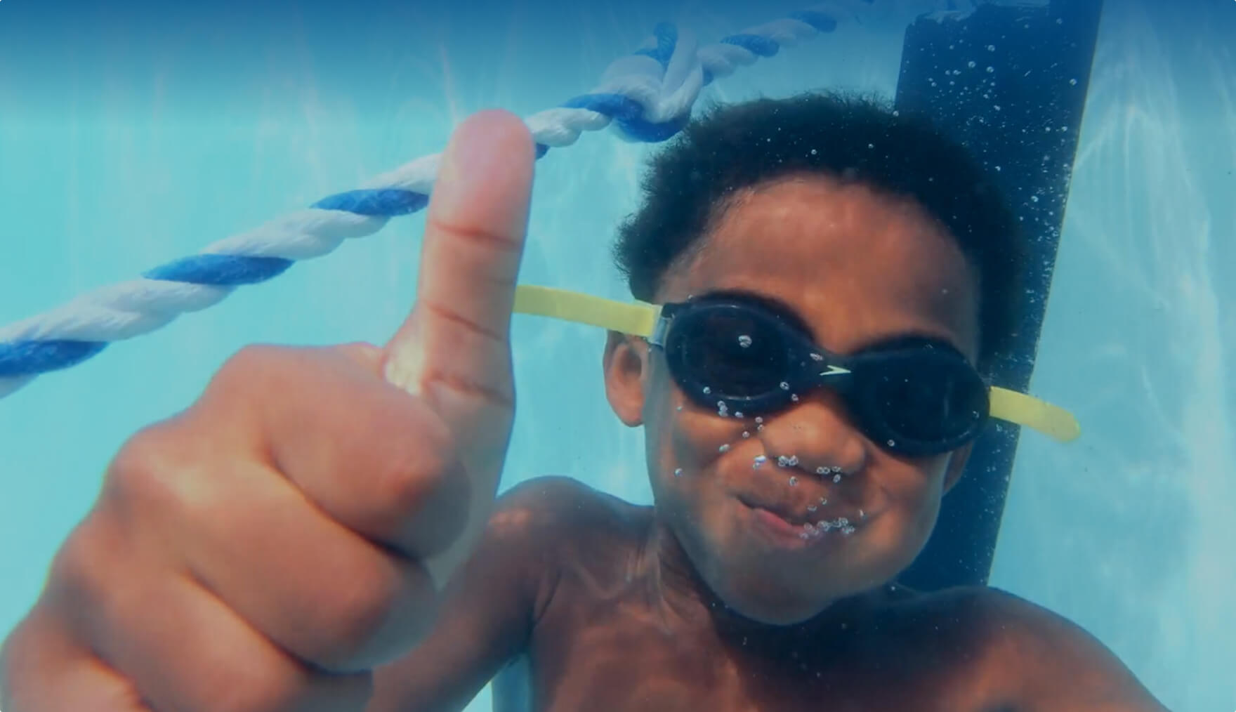 Child swimming in a pool wearing goggles